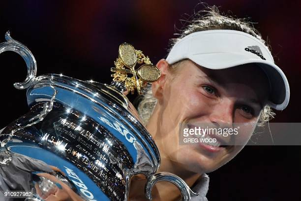 TOPSHOT Denmark's Caroline Wozniacki poses with the winner's trophy after beating Romania's Simona Halep in their women's singles final match on day...