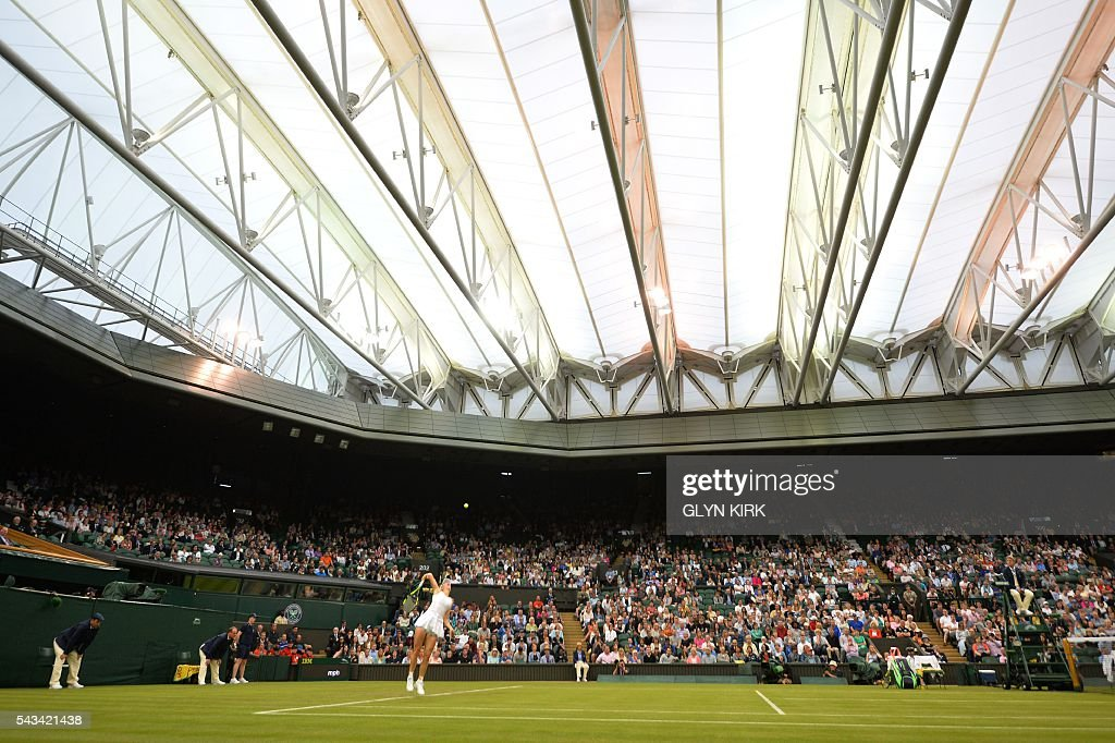 TOPSHOT - Denmark's Caroline Wozniacki serves against Russia's Svetlana Kuznetsova under the roof on Centre Court during their women's singles first round match on the second day of the 2016 Wimbledon Championships at The All England Lawn Tennis Club in Wimbledon, southwest London, on June 28, 2016. / AFP / GLYN