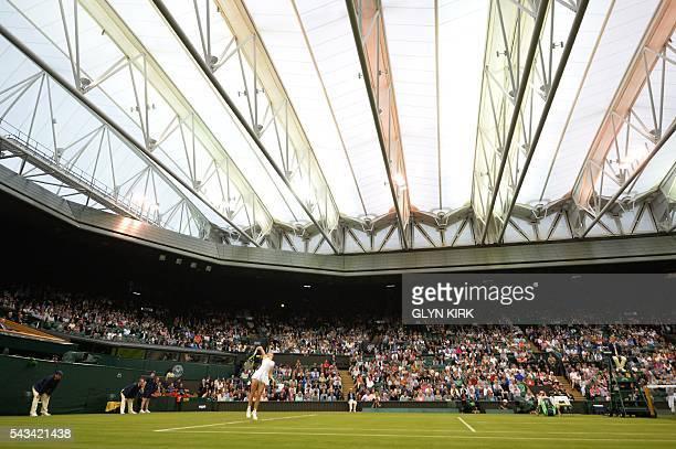 TOPSHOT Denmark's Caroline Wozniacki serves against Russia's Svetlana Kuznetsova under the roof on Centre Court during their women's singles first...