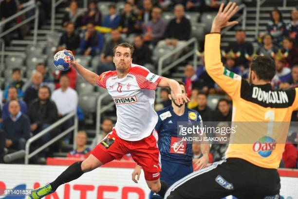 Denmark's Casper U Mortensen jumps to shoot against France's goalkeeper Cyril Dumoulin during the match for third place of the Men's 2018 EHF...