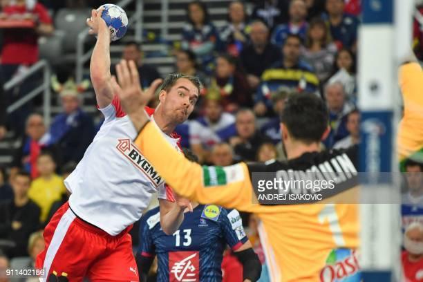 Denmark's Casper U Mortensen jumps to shoot against France's goalkeeper Cyril Dumoulin during the match for third place of the Men's 2018 EHF...