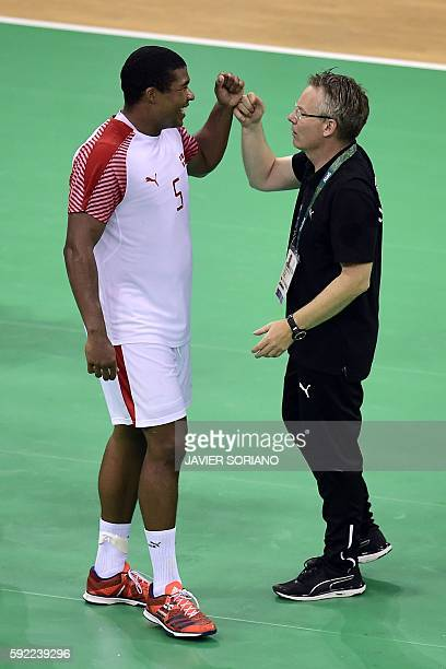 Denmark's coach Gudmundur Gudmundsson and Denmark's centre back Mads Mensah Larsen celebrate their victory and qualification for the final at the end...