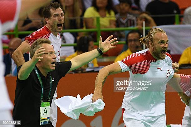 Denmark's coach Gudmundur Gudmundsson and Denmark's right back Kasper Sondergaard celebrate their victory and qualification for the final at the end...