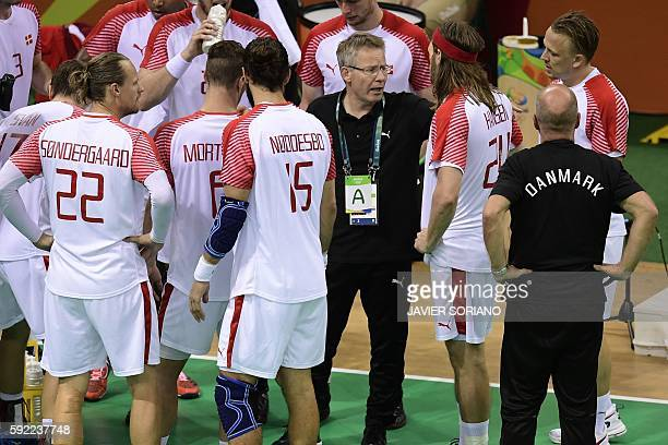 Denmark's coach Gudmundur Gudmundsson gives instructions to his players during a time out of the men's semifinal handball match Poland vs Denmark for...