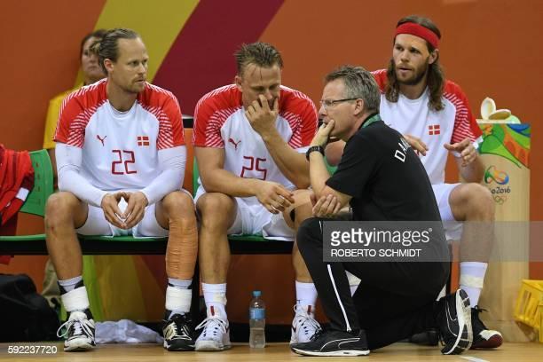 Denmark's coach Gudmundur Gudmundsson looks on past Denmark's right back Kasper Sondergaard Denmark's centre back Morten Olsen and Denmark's left...