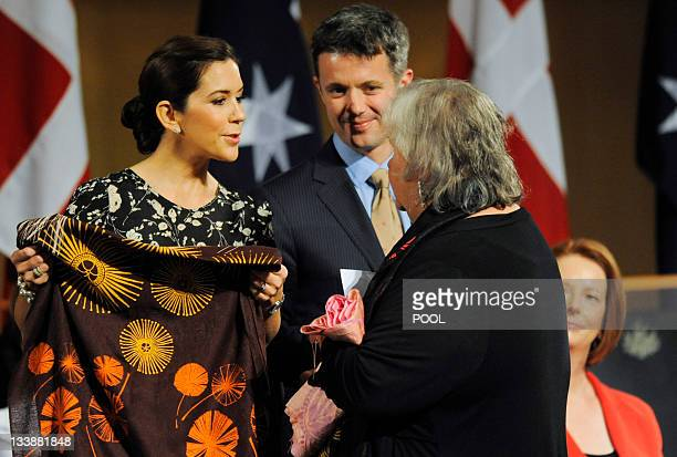 Denmark's Crown Prince Frederik and Crown Princess Mary receive a present from a local aboriginal elder prior to a luncheon hosted by Australian...