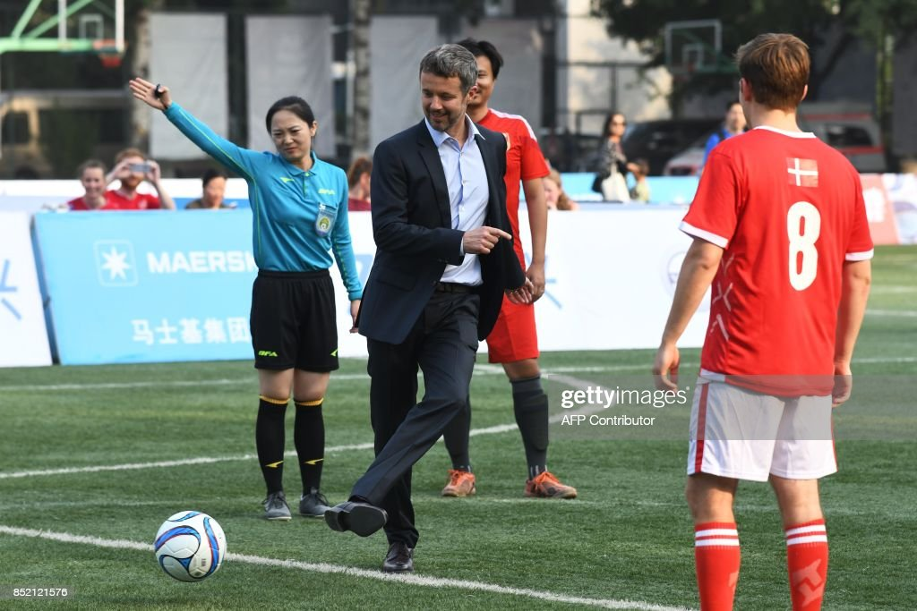 Denmark's Crown Prince Frederik (C) kicks the ball to start the final of the Sino-Nordic Cup football tournament between Denmark and a Chinese team in Beijing on September 23, 2017. The Crown Prince is on a four-day visit to China. /