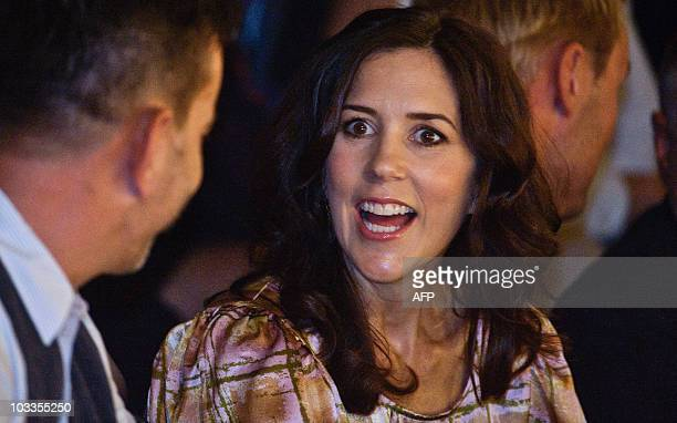 Denmark's Crown Princess Mary talks to an unidentified guest during a fashion show by Londonbased Danish designer Peter Jensen in Copenhagen on...