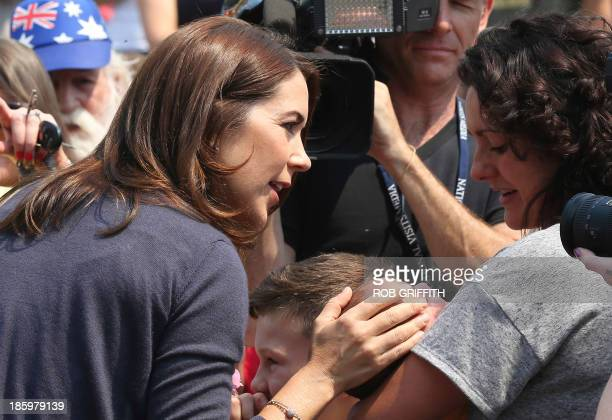 Denmark's Crown Princess Mary touches a young child and speaks to the child's mother in the crowd during a visit to the Winmalee fire station 85 kms...