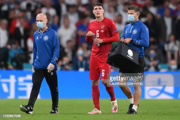 Denmark's defender Andreas Christensen leaves the football pitch after he is injurred during the UEFA EURO 2020 semi-final football match between...