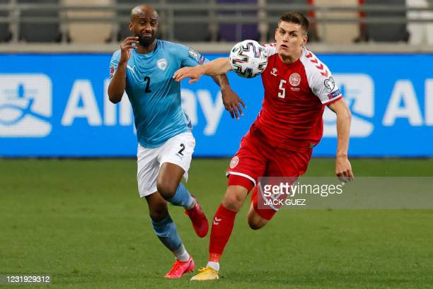 Denmark's defender Joakim Maehle vies for the ball with Israel's defender Eli Dasa during the 2022 FIFA World Cup qualifier group F football match...