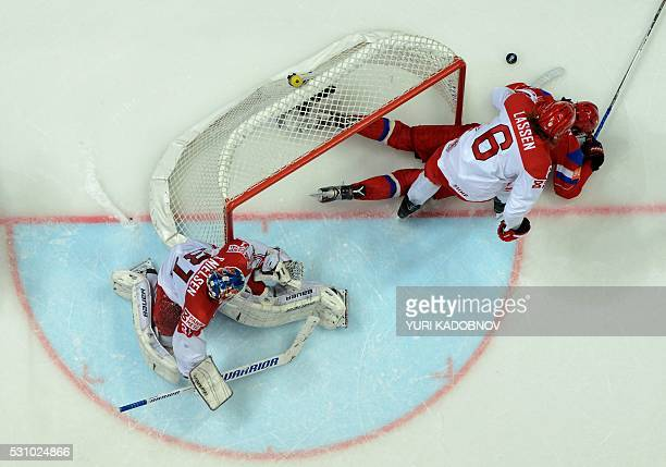 Denmark's defender Stefan Lassen vies with Russia's forward Ivan Telegin next to Denmark's goalie Simon Nielsen during the group A preliminary round...