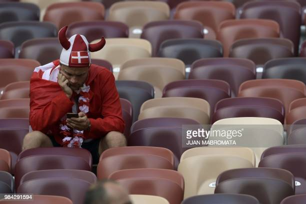 A Denmark's fan with a Viking helmet checks his smartphone as he waits before the Russia 2018 World Cup Group C football match between Denmark and...