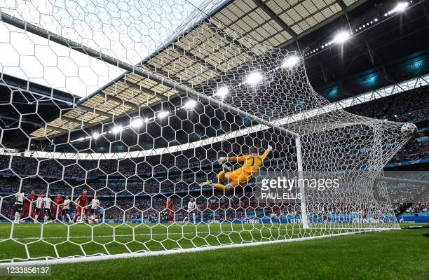 Denmark's forward Mikkel Damsgaard shoots and scores his team's first goal past England's goalkeeper Jordan Pickford during the UEFA EURO 2020...