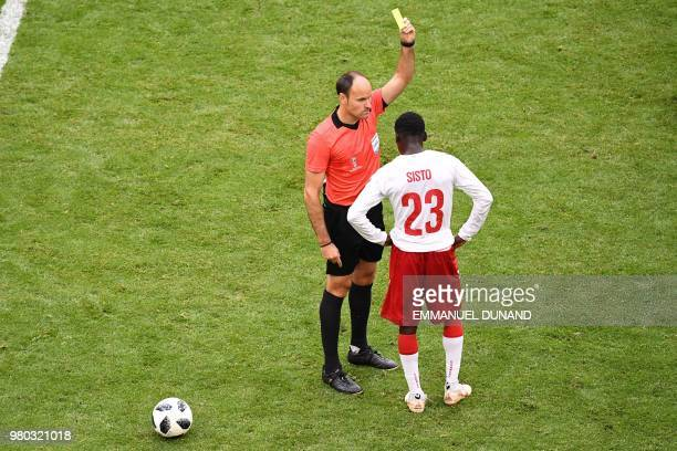 Denmark's forward Pione Sisto receives a yellow card from Spanish referee Antonio Mateu Lahoz during the Russia 2018 World Cup Group C football match...