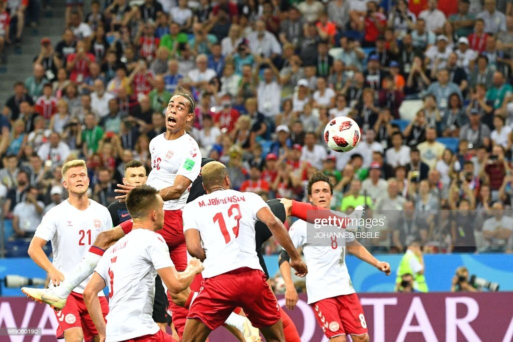 Denmark's forward Yussuf Poulsen (top) heads the ball during the Russia 2018 World Cup round of 16 football match between Croatia and Denmark at the Nizhny Novgorod Stadium in Nizhny Novgorod on July 1, 2018. (Photo by Johannes EISELE / AFP) / RESTRICTED