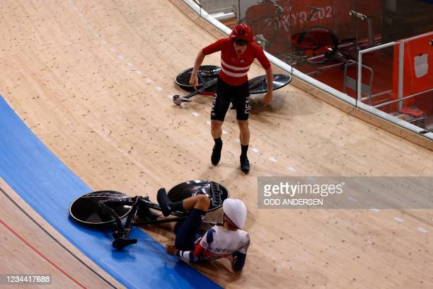 Denmark's Frederik Madsen reacts after crashed with Great Britain's Charlie Tanfiled during the first round heats of the men's track cycling team...