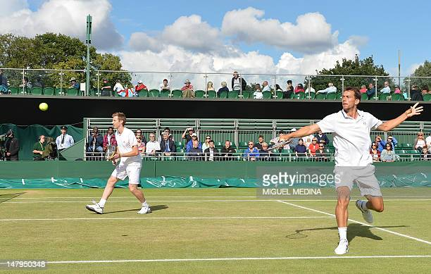 Denmark's Frederik Nielsen returns a shot as his partner Britain's Jonathan Marray looks on during their men's doubles semifinal victory over US...