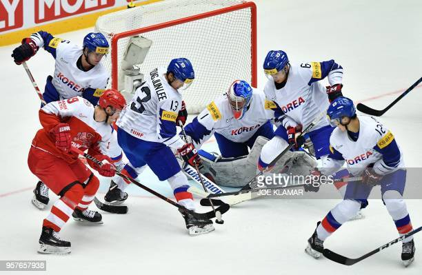 Denmark's Frederik Storm struggles for the puck with South Korean players during the group B match Denmark vs Korea of the 2018 IIHF Ice Hockey World...