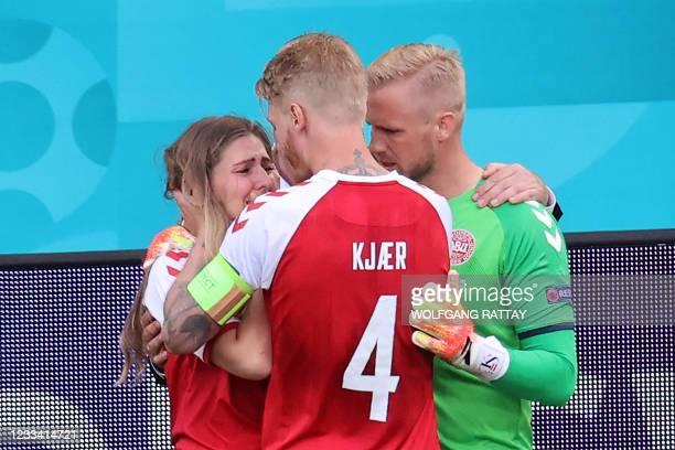 Denmark's goalkeeper Kasper Schmeichel and Denmark's defender Simon Kjaer comfort Sabrina Kvist Jensen, partner of Denmark's midfielder Christian...