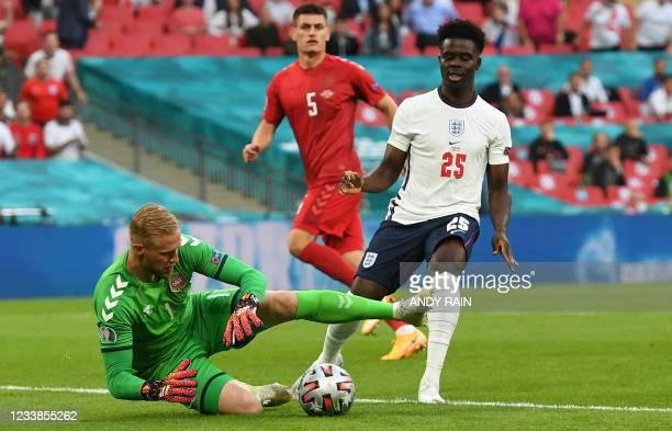 Denmark's goalkeeper Kasper Schmeichel catches the ball in front of England's midfielder Bukayo Saka during the UEFA EURO 2020 semi-final football...