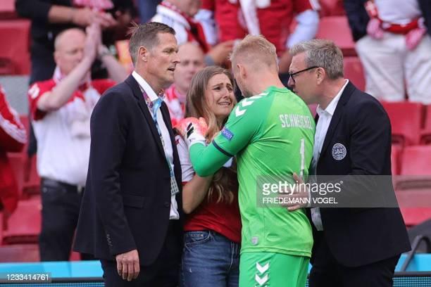 Denmark's goalkeeper Kasper Schmeichel comforts Sabrina Kvist Jensen, partner of Denmark's midfielder Christian Eriksen, after he collapsed on the...