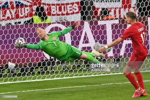 Denmark's goalkeeper Kasper Schmeichel saves a shot during the UEFA EURO 2020 semi-final football match between England and Denmark at Wembley...