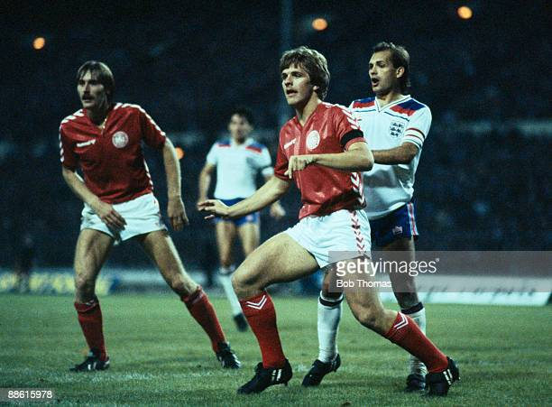 Denmark's Jan Molby is marked by England's Ray Wilkins as Ivan Nielsen looks on during the European Championship Qualiyfing match at Wembley Stadium...