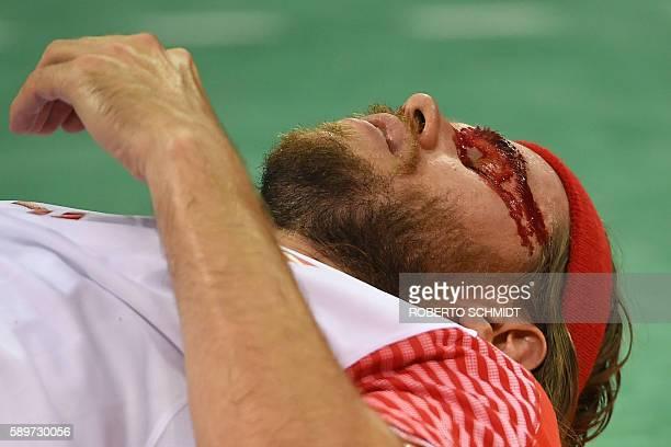 Denmark's left back Mikkel Hansen lies on the floor as he eyebrow bleeds during the men's preliminaries Group A handball match France vs Denmark for...