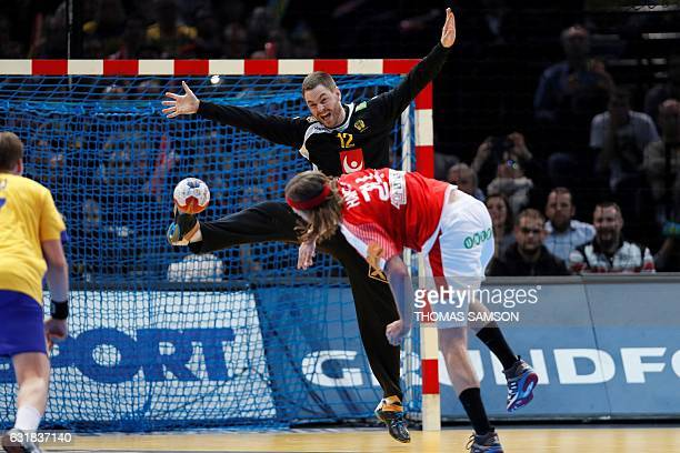TOPSHOT Denmark's left back Mikkel Hansen scores a penalty to Sweden's goalkeeper Andreas Palicka during the 25th IHF Men's World Championship 2017...