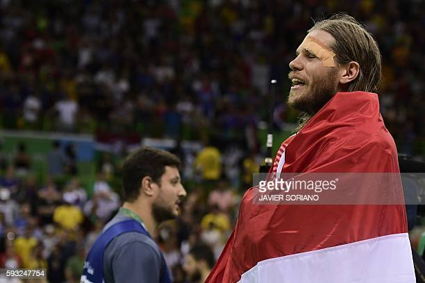 Denmark's left back Mikkel Hansen wrapped with a national flag celebrates their victory at the end of the the men's Gold Medal handball match Denmark...
