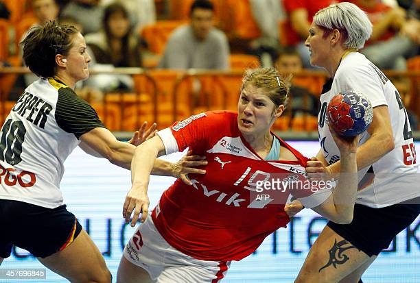 Denmark's Lyne Anna Ryborg Jorgensen vies with Germany's Anna Loerper and Anja Althaus during the Women's Handball World Championship 2013 quarter...