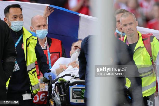 Denmark's midfielder Christian Eriksen is evacuated after collapsing on the pitch during the UEFA EURO 2020 Group B football match between Denmark...