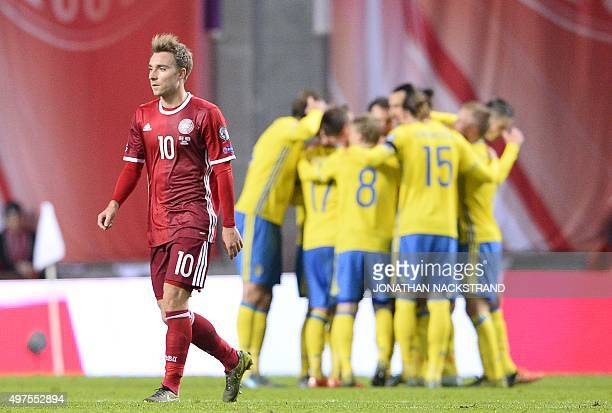 Denmark's midfielder Christian Eriksen reacts as Sweden's forward and team captain Zlatan Ibrahimovic celebartes with teammates after scoring a goal...