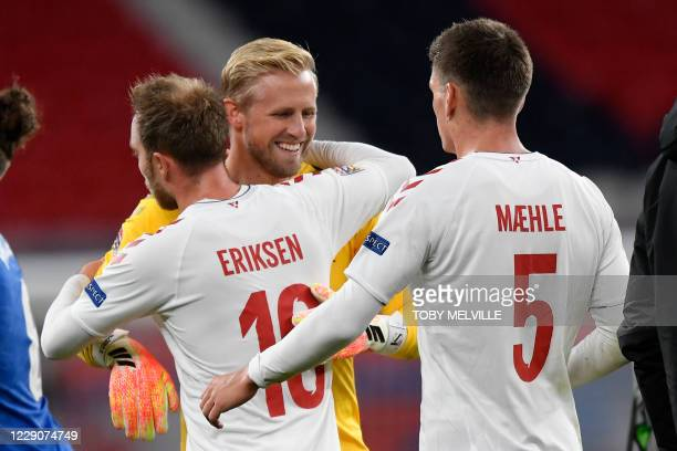 Denmark's midfielder Christian Eriksen reacts with Denmark's goalkeeper Kasper Schmeichel at the final whistle during the UEFA Nations League A2...