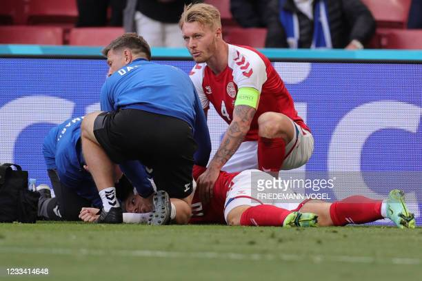 Denmark's midfielder Christian Eriksen receives medical attention after collapsing on the pitch during the UEFA EURO 2020 Group B football match...