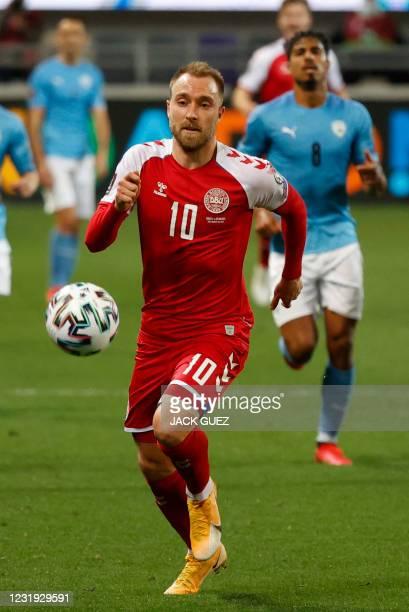 Denmark's midfielder Christian Eriksen runs after the ball during the 2022 FIFA World Cup qualifier group F football match between Israel and Denmark...