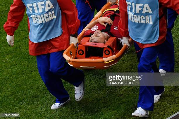 TOPSHOT Denmark's midfielder William Kvist is stretchered off the pitch with an injury during the Russia 2018 World Cup Group C football match...