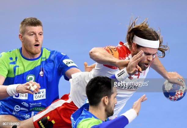 Denmark's Mikkel Hansen vies with Slovenia's Blaz Blagotinsek and Igor Zabic during the group II match of the Men's 2018 EHF European Handball...
