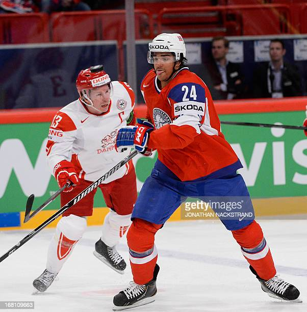Denmark's Morten Green and Norway's Andreas Martinsen vie for the puck during the preliminary round match Norway vs Denmark at the 2013 IIHF Ice...