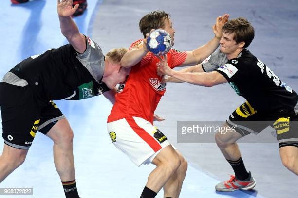 Denmark's Morten Toft Olsen vies with Germany's Patrick Wiencek and Rune Dahmke during the group II match of the Men's 2018 EHF European Handball...