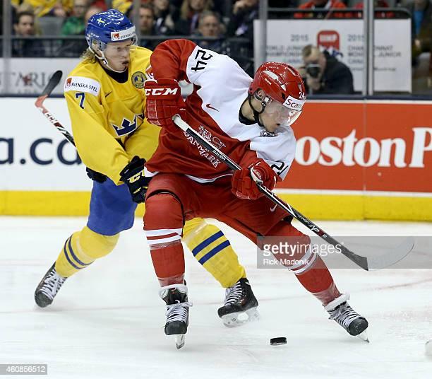 TORONTO DECEMBER 27 Denmark's Nikolaj Ehlers loses his check Sweden's Julius Bergman in front of the net 2015 IIHF World Junior Championship hockey...