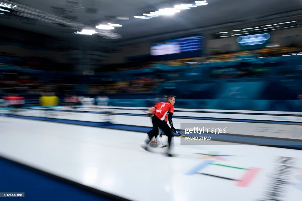 Denmark's Oliver Dupont brushes the ice surface during the curling men's round robin session between Denmark and Sweden during the Pyeongchang 2018 Winter Olympic Games at the Gangneung Curling Centre in Gangneung on February 14, 2018. / AFP PHOTO / WANG Zhao