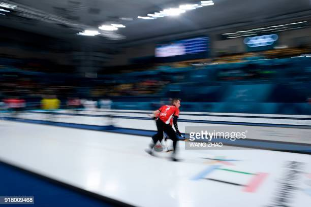 Denmark's Oliver Dupont brushes the ice surface during the curling men's round robin session between Denmark and Sweden during the Pyeongchang 2018...