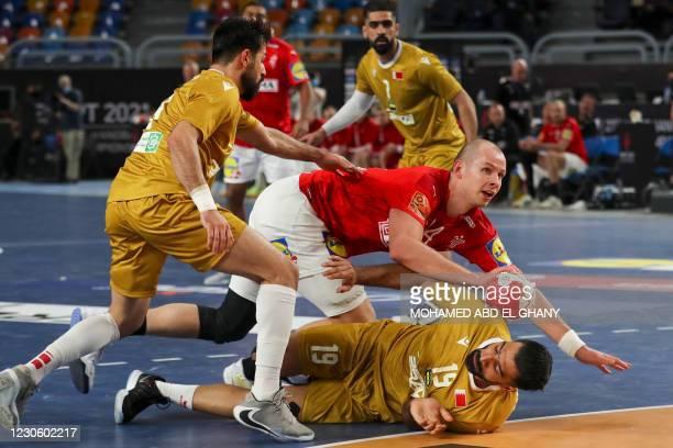Denmark's pivot Simon Hald Jensen is challenged by Qatar's right winger Marwane Sassi during the 2021 World Men's Handball Championship match between...
