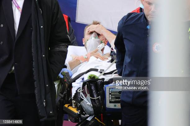 Denmark's players escort Denmark's midfielder Christian Eriksen as he is evacuated after collapsing on the pitch during the UEFA EURO 2020 Group B...