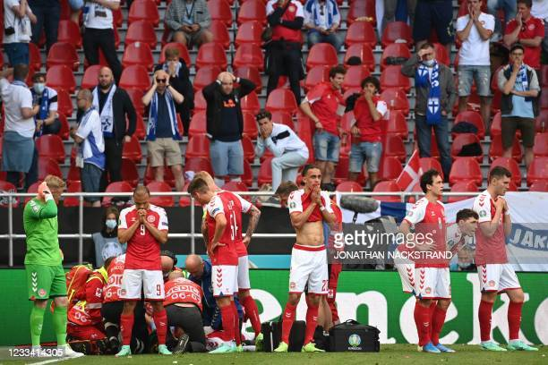Denmark's players gather as paramedics attend to midfielder Christian Eriksen during the UEFA EURO 2020 Group B football match between Denmark and...