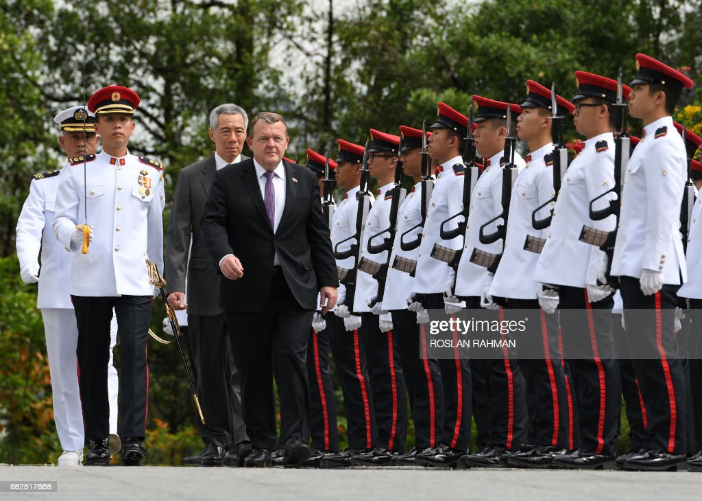 Denmark's Prime Minister Lars Lokke Rasmussen (C) is followed by Singapore's Prime Minister Lee Hsien Loong (behind) as they inspect a guard of honour during a welcoming ceremony at the Istana presidential palace in Singapore on November 30, 2017. The Danish prime minister is on a two-day official visit. /