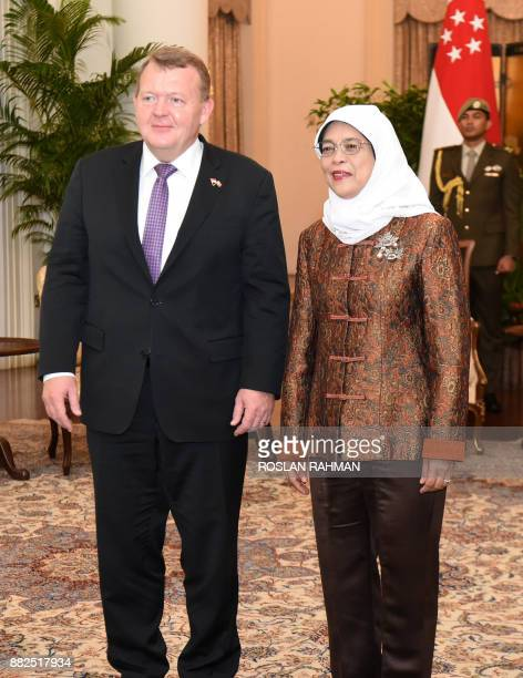 Denmark's Prime Minister Lars Lokke Rasmussen poses with Singapore President Halimah Yacob for photographers during their meeting at the Istana...