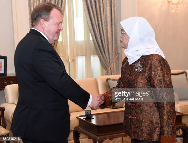 Denmark's Prime Minister Lars Lokke Rasmussen shakes hands with Singapore President Halimah Yacob during their meeting at the Istana presidential...